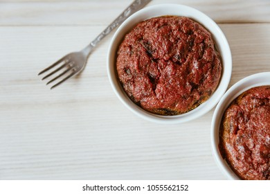 Healthy vegan beetroot muffins in white cups on wooden background with vintage fork. Festive composition, copy space available. Flat lay. Film style.