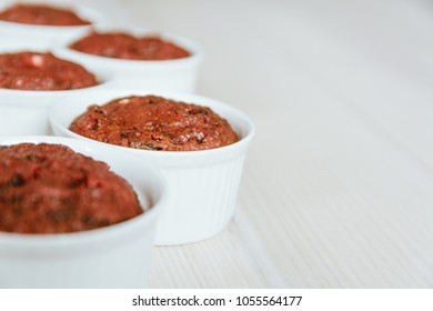 Healthy vegan beetroot muffins in white cups on light wooden background. Festive composition, shallow depth of field, copy space available.