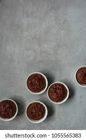 Healthy vegan beetroot muffins in white cups on rustic grey board. Festive composition, copy space available. Flat lay. Film style.