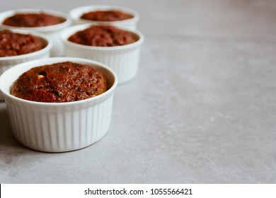 Healthy vegan beetroot muffins in white cups on rustic bord. Festive composition, copy space available, shallow depth of field. Film style.