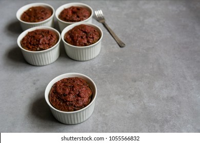Healthy vegan beetroot muffins in white cups and vintage fork on rustic bord. Festive composition, copy space available, shallow depth of field. Vintage style.