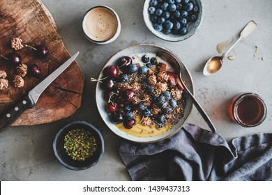 Healthy vegan breakfast. Flat-lay of quinoa oat granola coconut yogurt bowl with fresh fruit, honey, seed, nut, berries and cup of coffee over grey background, top view. Clean eating food concept