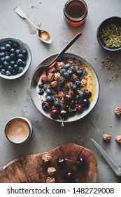 Healthy vegan breakfast. Flat-lay of quinoa oat granola coconut yogurt bowl with fruit, honey, seeds, nuts, berries and cup of coffee over grey concrete background, top view. Clean eating food concept