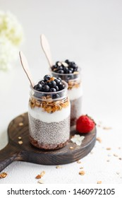 Healthy vegan breakfast with fresh blueberries, yogurt, granola and chia pudding in glass on wooden board and white background. Detox and dieting food. Copy space.
