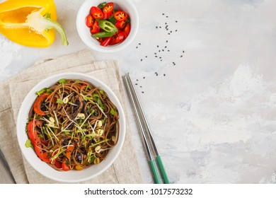 Healthy vegan buckwheat noodles with a mix of vegetables, sprouts and nut-soy sauce. Vegetarian padthai soba noodles in white bowl. Copy space, top view