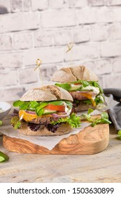 Healthy vegan burger with fresh vegetables and yogurt sauce on rustic kitchen counter top.