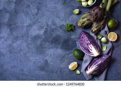 Healthy vegan cooking ingredients, fresh vegetables, clean eating concept, artichokes,brussel sprouts and red cabbage, copy space background