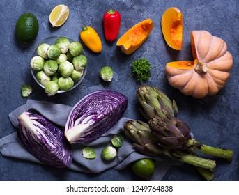 Healthy vegan cooking ingredients, fresh vegetables, artichokes, pumpkins, clean eating concept, flat lay