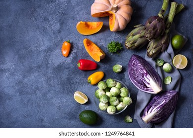 Healthy vegan cooking ingredients, fresh vegetables, clean eating concept, copy space background, flat lay. red cabbage, artichokes, brussel sprouts, pumpkin, top view