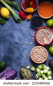 Healthy vegan cooking ingredients, fresh vegetables, clean eating concept, artichokes, brussel sprouts, red cabbage, quinoa, chickpeas, lentils, top view copy space background