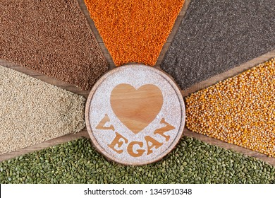 Healthy vegan diet choices concept with colorful seeds and grains surrounding cutting board with heart shape drawn in flour