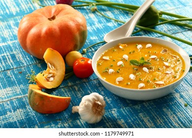 Healthy vegan diet food- Delicious autumn butternut squash soup with cream and herbs.on a wooden background.