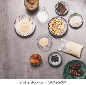 Healthy vegan diet ingredients bowls : cashew , almond flour, Coconut cream, non dairy milk, agar agar, Coconut butter, dried fruits on concrete background, top view. Plant based and Low-calorie diet