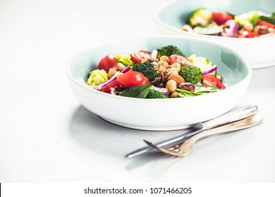 Healthy vegan energy boosting salad with chickpeas, broccoli, tomatoes, red onion, spinach and nuts in blue plate on concrete background, selective focus. Clean eating, superfood, detox food concept