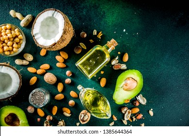 Healthy vegan fat food sources, omega3, omega6 ingredients - almond, pecan, hazelnuts, walnuts, olive oil, chia seeds, avocado, coconut, dark green background copy space
