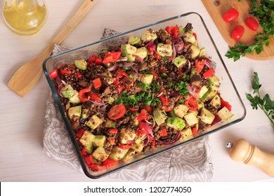 Healthy vegan food. Brown lentils cooked in an oven with tomatoes, zucchinis and other vegetables. Roasted lentils with veggies in a glass baking tray