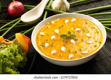 Healthy vegan food concept-Organic  pumpkin fresh cream soup on a wooden table.