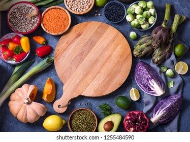 Healthy vegan food, cooking ingredients with fresh vegetables, quinoa, lentils, chickpeas, blank cutting board, copy space background, glat lay