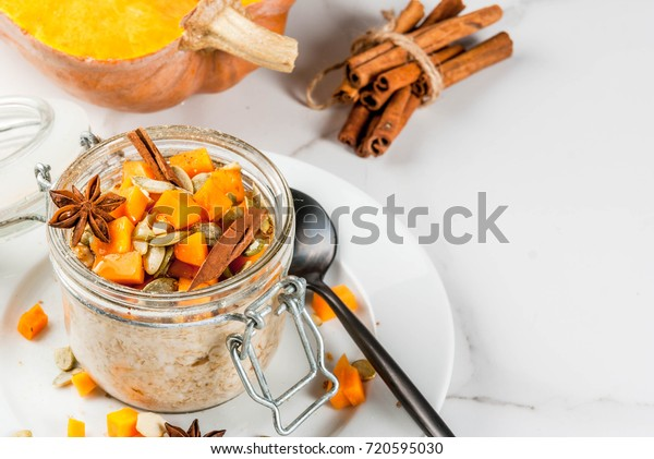 Healthy vegan food. Dietary breakfast or snack. Pumpkin pie overnight oats, with  pumpkin, yogurt, cinnamon, spices. In a glass, on a white marble table. Copy space