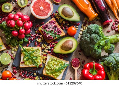 Healthy vegan food. Fresh vegetables on wooden background. Detox diet. Different colorful fresh juices.