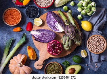Healthy vegan food, quinoa, lentils, chickpeas, cooking ingredients with fresh vegetables, clean eating concept, artichokes, mangold, brussel sprouts and red cabbage, flat lay