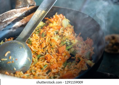 Healthy vegan food - vegetable pilaf or biryani from Indian cuisine, close up. Cooking vegetable biryani in an street cafe on a local market in India.