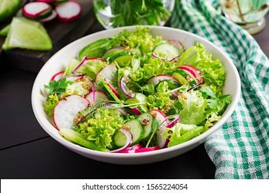 Healthy vegan food. Vegetarian vegetable salad of radish, cucumbers, lettuce  and red onion.