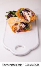 Healthy vegan fried vegetable wrap with salad, arugula, spinach, carrot and cabbage. Vegetarian raw food concept