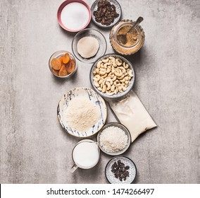 Healthy vegan gluten-free cake ingredients: cashew , almond flour, Coconut cream, non dairy milk, agar agar, Coconut butter, dried fruits on concrete background, top view. Plant based diet dessert