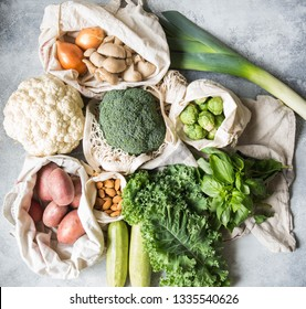 Healthy vegan ingredients for cooking. Various clean wholesome vegetables and herbs in woven bags. Products from the market without plastic. Zero waste concept flat lay.