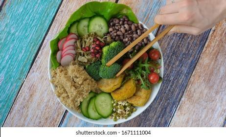 Healthy Vegan Lunch Bowl. Avocado, Quinoa, Chickpea Patty, Salad, Broccoli, Beans.