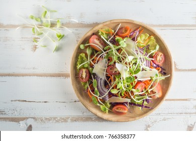Healthy vegan lunch dish.Tomato, cucumber, red cabbage, carrot, onion and microgreens vegetables salad on wooden plate. Top view