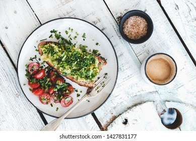 Healthy vegan lunch. Flat-lay of avocado toast on sourdough bread with chives, coriander, cherry-tomatoes with cup of coffee over white background, top view. Vegetarian, clean eating concept