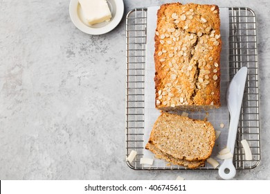 Healthy vegan oat and coconut  loaf bread, cake on a cooling rack Grey stone background Top view Copy space