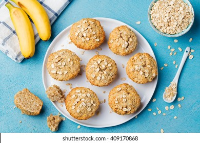 Healthy vegan oat muffins, apple and banana cakes with sour cream on a white plate Blue stone background Top view