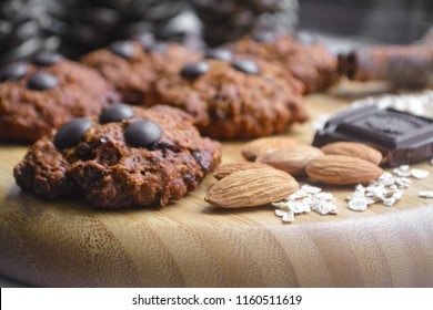 Healthy vegan oatmeal chocolate chip cookies with almonds and cinnamon on a wooden plate decorated with dark chocolate, quick oats, cinnamon sticks, almonds and pine cones