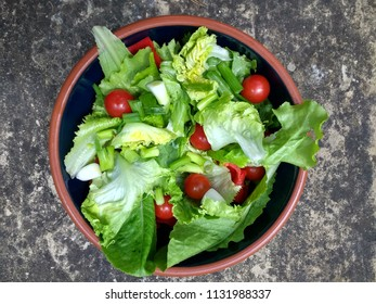 Healthy vegan organic Summer salad of home grown garden vibrant green lettuce leaves, red tomatoes peppers onion in blue ceramic bowl earthenware rim against background of grey stone viewed above