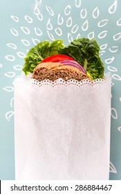 Healthy vegan sandwich wrapped in white paper