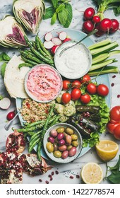 Healthy vegan snack set. Flat-lay of beetroot hummus, yogurt, herb dip, olives, flatbread, cous cous, dolma, vegetables and fruit on tray over marble background, top view. Clean eating food concept