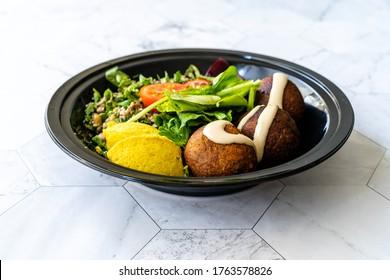 Vegan sain Emporter le Falafel Bowl avec de la salade de seins Mung, de la légumineuse, de la betterave rôtie et de la sauce Tahini à Turmeric jaune dans le paquet de la Coupe de Plastique Noire / Conteneur sur la surface du marbre.