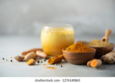 Healthy vegan turmeric latte or golden milk, turmeric root, ginger powder, black pepper over grey concrete background. Spices for ayurvedic treatment. Alternative medicine concept.
