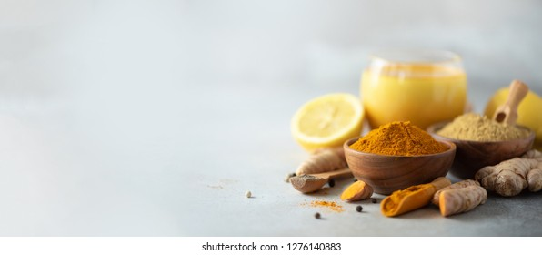 Healthy vegan turmeric latte or golden milk, turmeric root, ginger powder, black pepper over grey background. Spices for ayurvedic treatment. Alternative medicine concept. Banner with copy space.