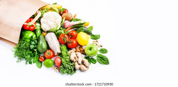 Healthy vegan vegetarian food in full paper bag, vegetables and fruits on white background, copy space, banner. Shopping food supermarket, groceries and clean eating concept. Healthy food background