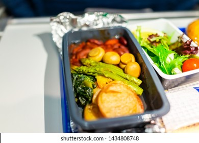 Healthy vegan vegetarian food hot vgml meal macro closeup on airplane flight with potato mushrooms asparagus vegetables on tray with salad