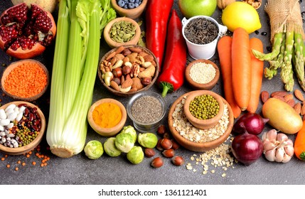 Healthy vegan and vegetarian food on black stone background. Superfoods, vegetables, fruits, nuts and grains. Diet eating concept. Banner. Panorama.