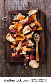 Healthy vegetable beetroot, sweet potato and white sweet potato chips on a black board with spoon of seasoning over rustic background. Top view