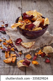 Healthy vegetable beetroot, sweet potato and white sweet potato chips on over rustic background