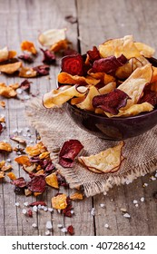 Healthy vegetable beetroot, sweet potato and white sweet potato chips on a bowl on a rustic background. Selective focus