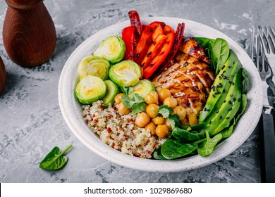Healthy vegetable buddha bowl lunch with grilled chicken and quinoa, spinach, avocado, brussels sprouts, red paprika and chickpea on gray background.