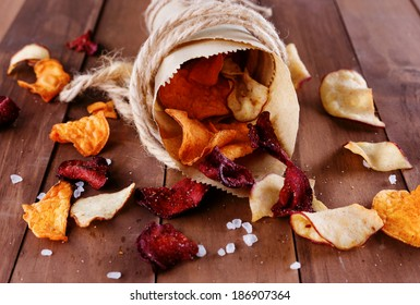 Healthy vegetable chips with sea salt in a vintage paper wrap on a rustic wooden background